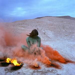 Woman sitting in orange smoke